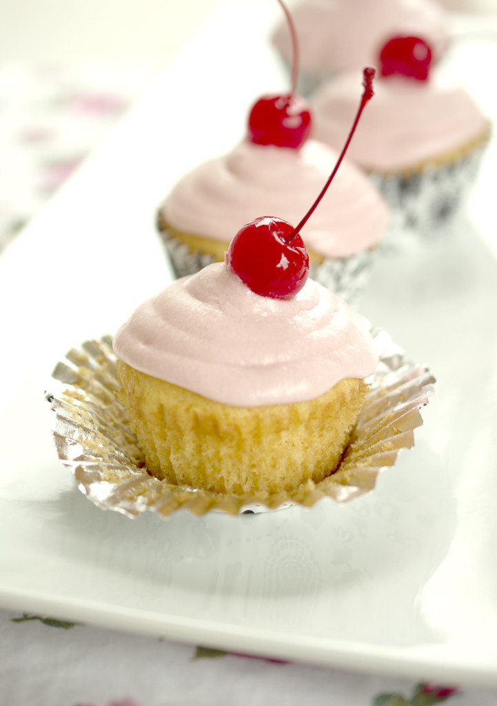 yellow cupcakes with cherry frosting