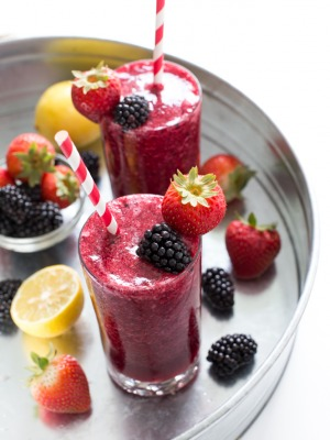 Top shot of berry slush drink in glass cups next to fresh berries.