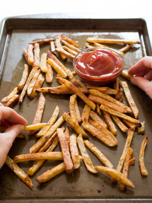 Hands picking up potato fries from baking sheet.