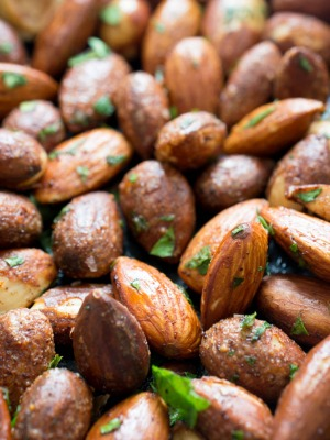 close up shot of spicy almonds with cilantro flakes